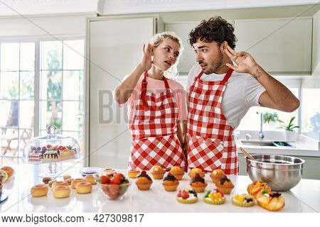 Couple of wife and husband cooking pastries at the kitchen smiling with hand over ear listening an hearing to rumor or gossip. deafness concept.
