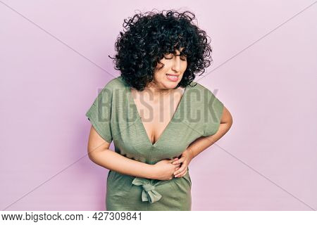 Young middle east woman wearing casual clothes with hand on stomach because indigestion, painful illness feeling unwell. ache concept.