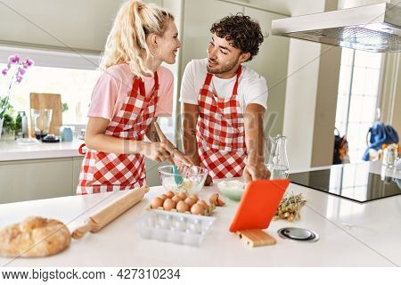 Young couple smiling happy mixing ingredients to make dough for homemade bread. Looking recipe on touchpad at kitchen.
