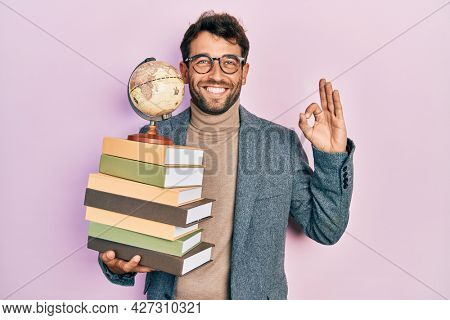 Handsome man with beard geography teacher doing ok sign with fingers, smiling friendly gesturing excellent symbol