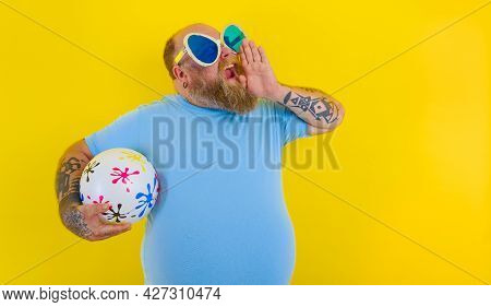 Fat Man With Beard And Sunglasses Screams With A Ball In Hand