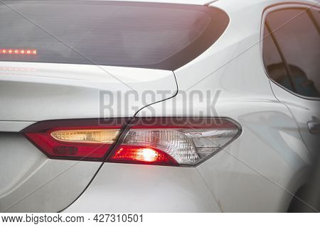 Abstract And Blurred Rear Side Of White Car Turn On Brake Light And Open Turn Rihgt Signal.