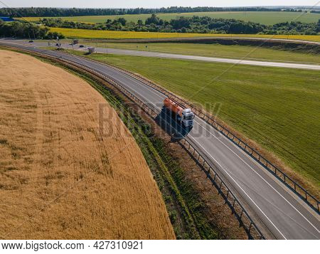 Moscow , Russia - JUN 23, 2021: Gasoline truck Oil trailer on highway driving along the road. aerial view of Tank vehicle at work