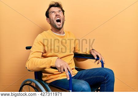 Handsome man with beard sitting on wheelchair angry and mad screaming frustrated and furious, shouting with anger. rage and aggressive concept.