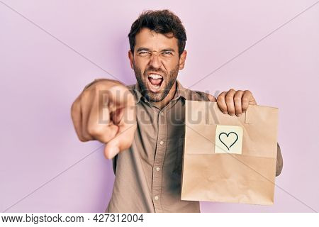 Handsome man with beard holding delivery paper bag with heart reminder pointing displeased and frustrated to the camera, angry and furious with you