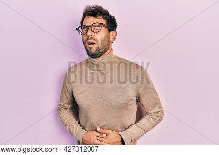 Handsome man with beard wearing turtleneck sweater and glasses with hand on stomach because nausea, painful disease feeling unwell. ache concept.