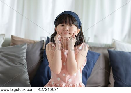 Portrait Of Asian Little Cute Girl With Happy Charming Smile In Living Room At Home.