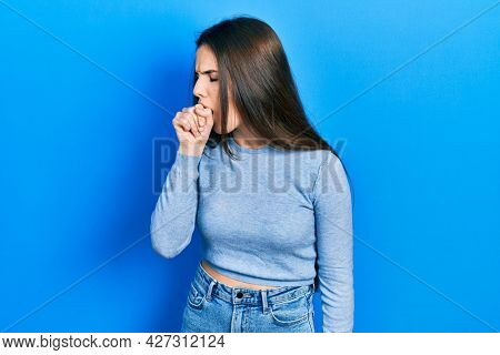 Young brunette teenager wearing casual sweater feeling unwell and coughing as symptom for cold or bronchitis. health care concept.
