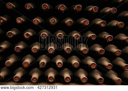 Bottles Of Old Wine In Dusty Cellars. Old Bottles Of In Wine Cellar