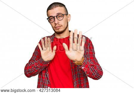 Hispanic young man wearing casual clothes moving away hands palms showing refusal and denial with afraid and disgusting expression. stop and forbidden.