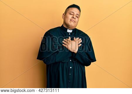 Young latin priest man standing over yellow background smiling with hands on chest with closed eyes and grateful gesture on face. health concept.