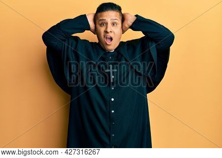 Young latin priest man standing over yellow background crazy and scared with hands on head, afraid and surprised of shock with open mouth
