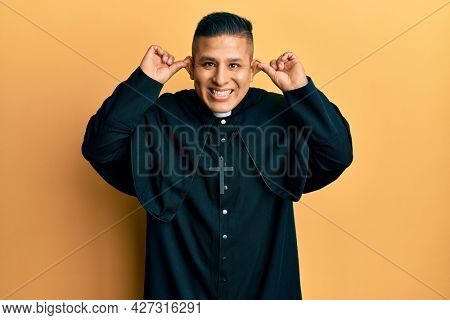 Young latin priest man standing over yellow background smiling pulling ears with fingers, funny gesture. audition problem