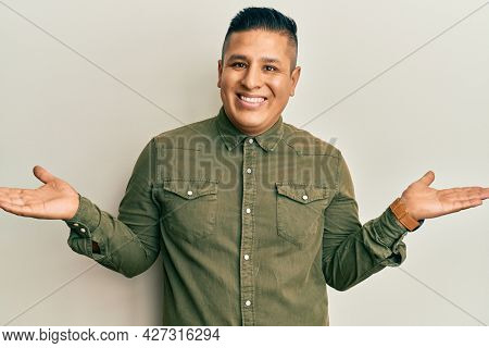 Young latin man wearing casual clothes smiling showing both hands open palms, presenting and advertising comparison and balance