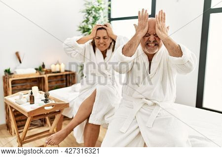 Middle age hispanic couple wearing bathrobe at wellness spa suffering from headache desperate and stressed because pain and migraine. hands on head.