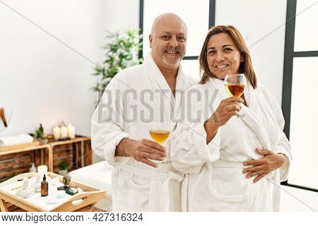 Middle age hispanic couple smiling happy toasting whit champagne at beauty center.