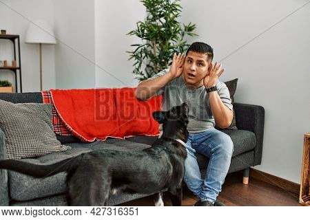 Young latin man and dog sitting on the sofa at home trying to hear both hands on ear gesture, curious for gossip. hearing problem, deaf