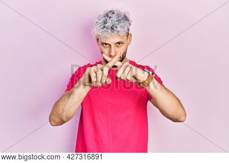 Young hispanic man with modern dyed hair wearing casual pink t shirt rejection expression crossing fingers doing negative sign