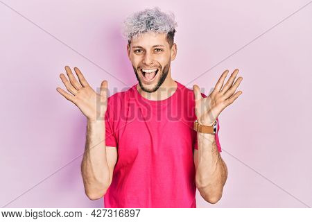 Young hispanic man with modern dyed hair wearing casual pink t shirt celebrating crazy and amazed for success with arms raised and open eyes screaming excited. winner concept