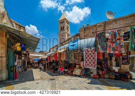 JERUSALEM, ISRAEL - JULY 16, 2018: View of narrow street with traditional  souvenir and carpet shops in Muristan - christian quarter in Old City of Jerusalem, popular place with tourists and pilgrims.