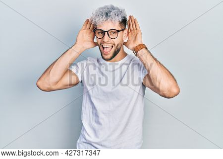 Young hispanic man with modern dyed hair wearing white t shirt and glasses smiling cheerful playing peek a boo with hands showing face. surprised and exited