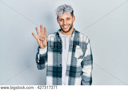 Young hispanic man with modern dyed hair wearing casual shirt showing and pointing up with fingers number four while smiling confident and happy.