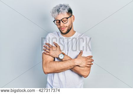 Young hispanic man with modern dyed hair wearing white t shirt and glasses hugging oneself happy and positive, smiling confident. self love and self care