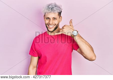 Young hispanic man with modern dyed hair wearing casual pink t shirt smiling doing phone gesture with hand and fingers like talking on the telephone. communicating concepts.