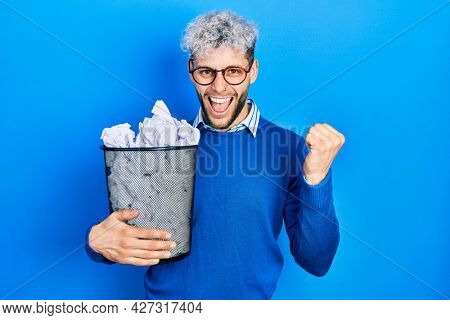 Young hispanic man with modern dyed hair holding paper bin full of crumpled papers screaming proud, celebrating victory and success very excited with raised arms