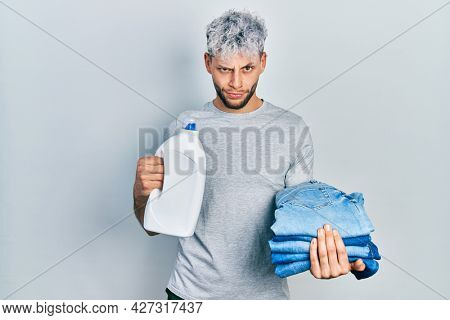 Young hispanic man with modern dyed hair holding jeans for laundry and detergent bottle skeptic and nervous, frowning upset because of problem. negative person.