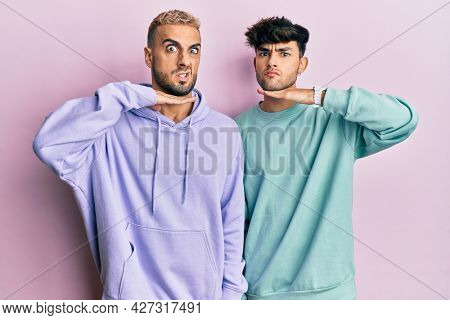 Homosexual gay couple standing together wearing casual clothes cutting throat with hand as knife, threaten aggression with furious violence