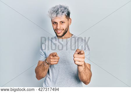 Young hispanic man with modern dyed hair wearing casual grey t shirt pointing fingers to camera with happy and funny face. good energy and vibes.