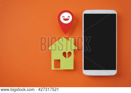 White Mobile Phone, Green House Paper Cut And Smiling Check In Symbol On Vivid Orange Background, Ho