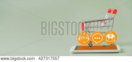 Shopping Cart And Contact Symbol On Yellow Circle Paper With Blurred Mobile Phone For Contact Us, Qu