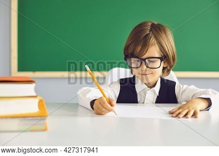 Back To School. Smart Schoolboy Writes With A Pencil While Sitting At A Table On The Background Of T