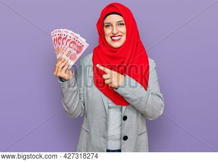 Beautiful hispanic woman wearing islamic hijab holding chinese yuan banknotes smiling happy pointing with hand and finger