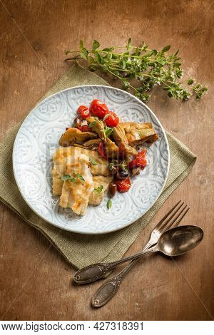 cooked cod with artichoke tomatoes olives capers and herbes