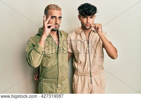 Homosexual gay couple standing together wearing casual jumpsuit mouth and lips shut as zip with fingers. secret and silent, taboo talking