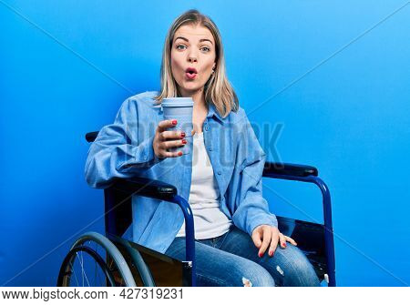 Beautiful caucasian woman sitting on wheelchair drinking a coffee scared and amazed with open mouth for surprise, disbelief face