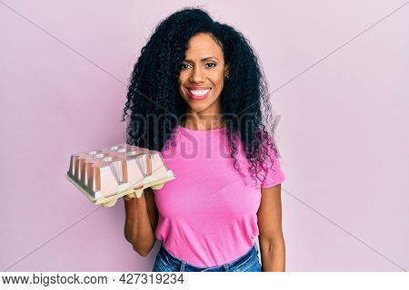 Middle age african american woman showing fresh white eggs looking positive and happy standing and smiling with a confident smile showing teeth