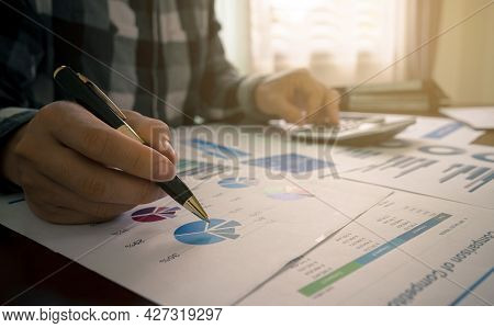 Businessman Or Accountant Working With A Pen In Her Hand Pointing Statistic Business Data And Calcul