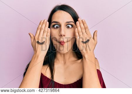Young hispanic woman covering eyes with hands and fake lashes making fish face with mouth and squinting eyes, crazy and comical.