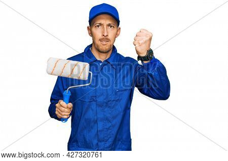 Bald man with beard holding roller painter annoyed and frustrated shouting with anger, yelling crazy with anger and hand raised