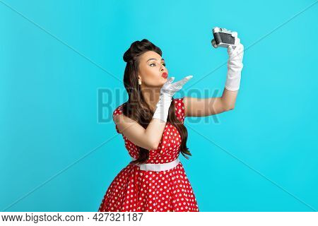 Sexy Young Pin Up Lady In Polka Dot Dress Taking Selfie With Retro Camera, Blowing Air Kiss On Blue