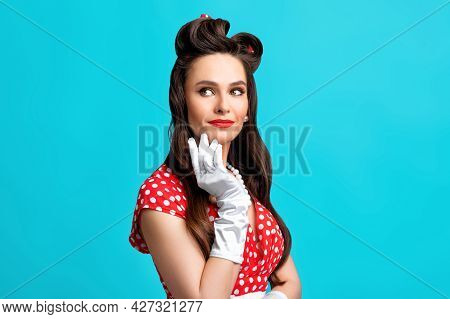 Beautiful Pinup Woman In Red Polka Dot Dress And Gloves Wearing Bright Makeup, Looking Aside On Blue