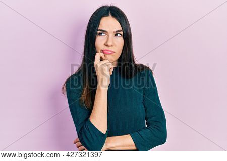 Young brunette woman wearing casual winter sweater thinking concentrated about doubt with finger on chin and looking up wondering