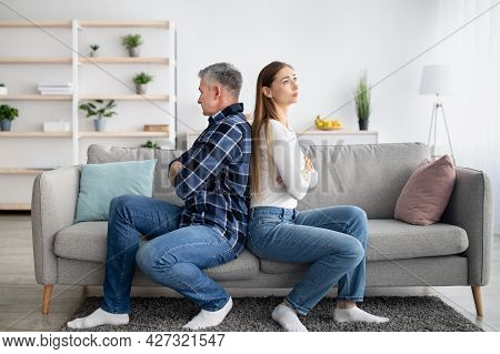 Middle Aged Married Couple Sitting Back To Back On Couch, Not Talking To Each Other After Conflict A
