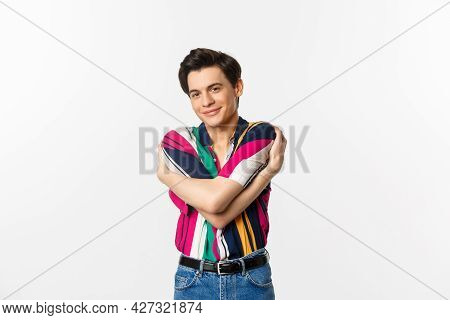 Happy Young Man Hugging Himself, Embracing Own Body And Smiling, Standing Against White Background