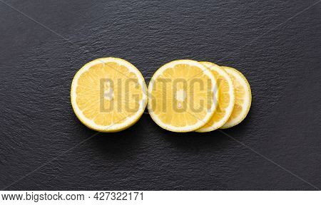 Sliced Lemon On A Black Background. Fresh Slices Of Citrus Fruit On A Stone Background. View From Ab