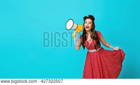 Young Pin Up Woman In Retro Dress Shouting Into Megaphone, Making Announcement On Blue Studio Backgr